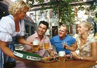 Biergarten - Kellnerin und Gäste in einem Biergarten