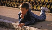 Bordsteinkante - An der Bordsteinkante liegender Junge