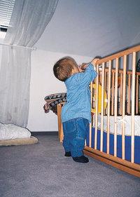Kleinkind - Kleinkind steht an einem Bett