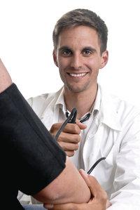 Manschette - Arzt bei der Blutdruckmessung