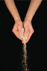 Sandkorn - Aus Händen rieselnde Sandkörner