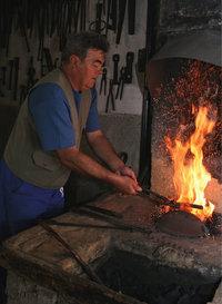 Schmiedefeuer - Ein Mann arbeitet am Schmiedefeuer