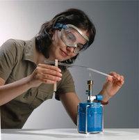 Schutzbrille - Die Frau trägt eine Schutzbrille beim Durchführen eines Versuches