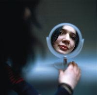 Spiegel - Spiegel, der das Gesicht einer Frau zeigt