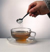 Teelöffel - Teelöffel mit Zucker und eine Tasse Tee