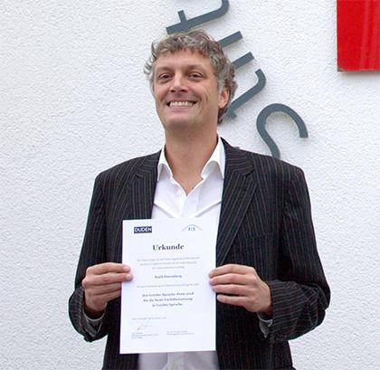 Mark Harenberg lächelt und zeigt eine Urkunde